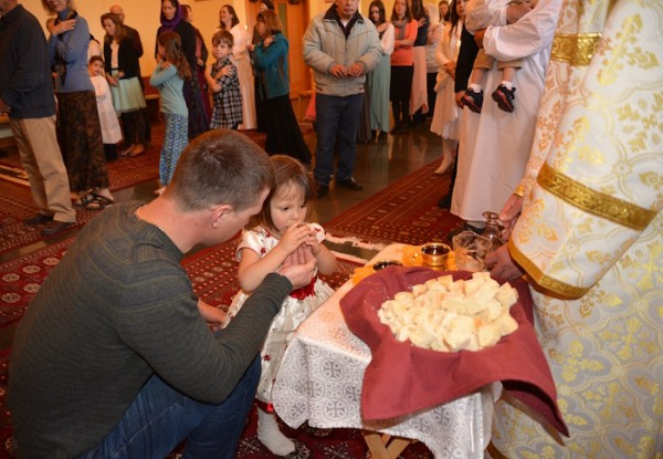 A child participates in the Divine Liturgy with the help of her godfather.